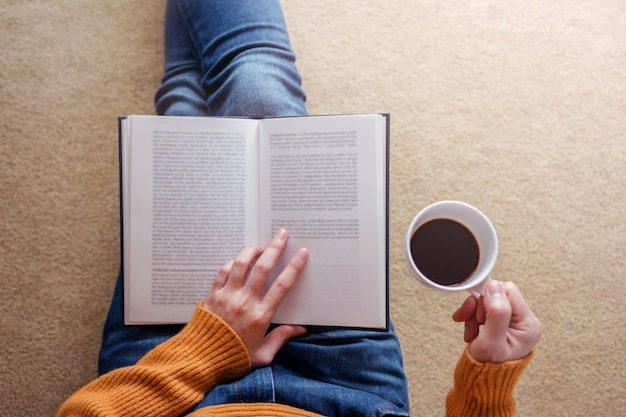 読書の概念。コージーハウスでの本とコーヒーでくつろいだ若い女性のソフトフォーカス