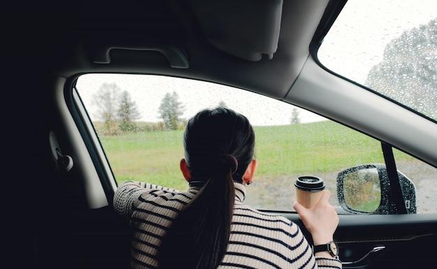 Дождливый день или плохая погода в концепции каникул. женщина, сидящая в машине и ожидая дождя