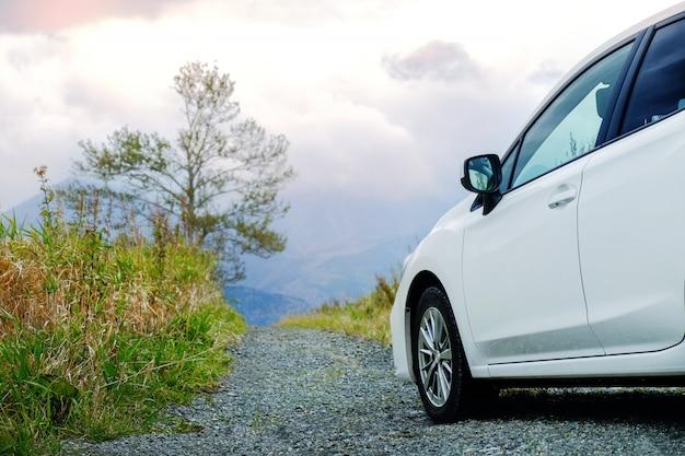 旅行のコンセプトです。田舎道で道路上の車、曇り空と山に車を運転
