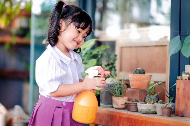 Счастливая милая азиатская девушка, наслаждающаяся садоводством, ребенок в школьной форме