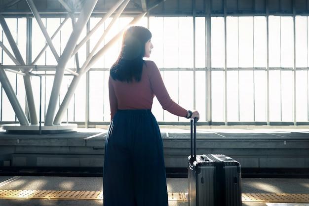 旅行のコンセプトです。駅でプラットフォームのスーツケースを待っている若い女性