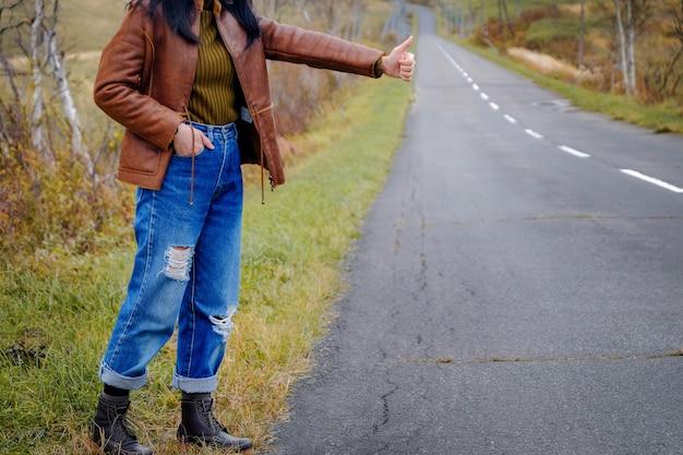 旅行と自由の概念道端に立っている若いヒッチハイカー旅行者女性