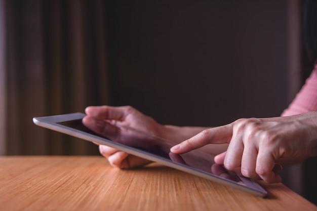 木製のテーブルにデジタルタブレットを使用して現代人