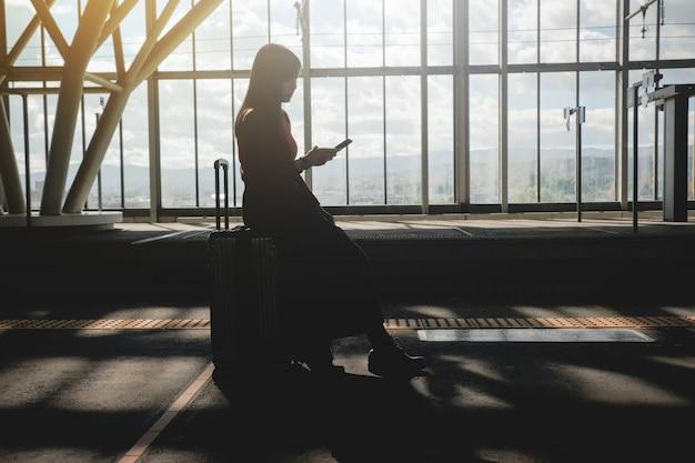 旅行のコンセプトです。駅でプラットホームにスーツケースを持って待っている若い女性。