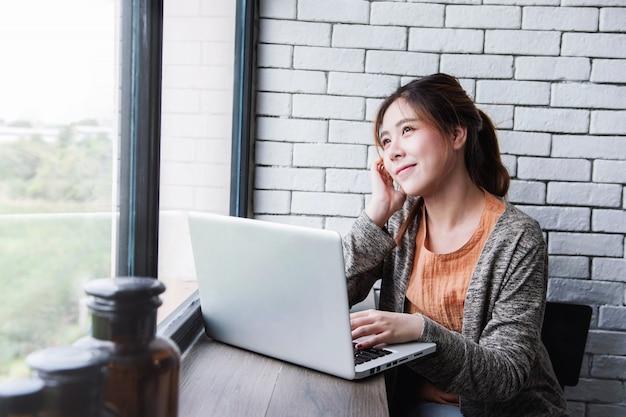 若いフリーランサーの女性居心地の良い家でコンピューターのラップトップに取り組んで、思いやりのある姿勢で窓の外を見て、新世代の人々のライフスタイル、成功を夢見て