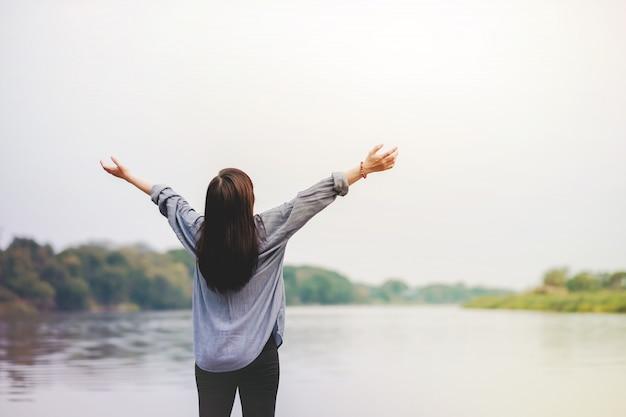 川のそばに立っている幸せな女。新鮮な空気を吸うために腕を上げる