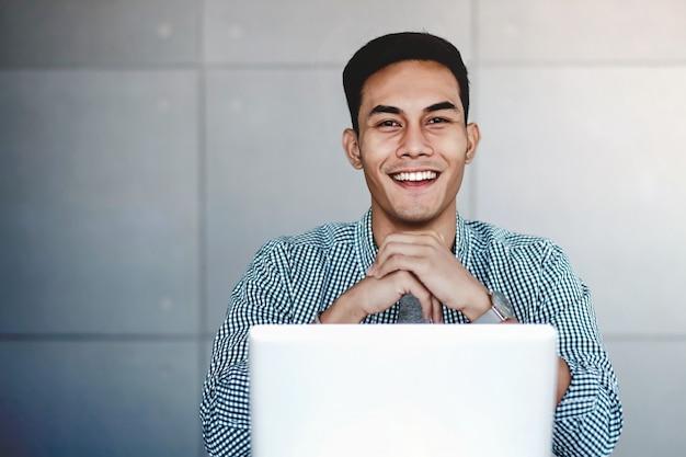 彼の職場でコンピューターのラップトップに取り組んで幸せな若いアジア系のビジネスマン