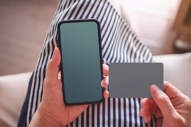スマートフォンとカードのモックアップ画像。携帯電話を保持している若い女性