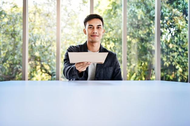 ガラス窓のオフィスのテーブルに座っている青年実業家のソフトフォーカス
