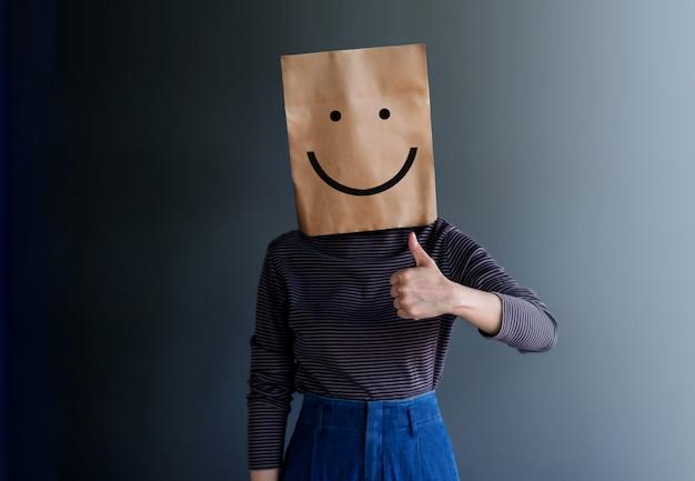 顧客経験または人間の感情的概念女性は紙袋で彼女の顔を覆い、描かれたライン漫画とボディーランゲージで現在の幸せな気持ち