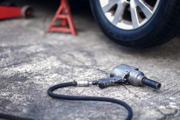 タイヤ交換のコンセプトです。ホイールナット用の電動ドライバーレンチはガレージの床に横たわっていました。車のメンテナンスとサービス