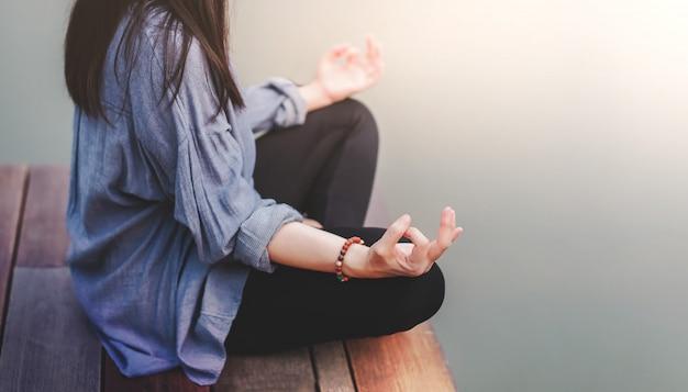 若い女性は屋外でヨガを練習します。蓮華座に座っています。アンプラグドライフとメンタルヘルスのコンセプト