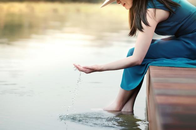アンプラグド生活や自然の概念と人間の生活。川辺でリラックスした幸せな若い女