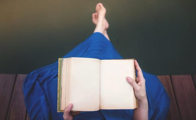 川辺でリラックスした若い女性。デッキに座っていると空白の本を読む