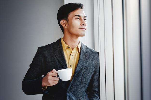 オフィスの窓のそばに立って幸せなビジネスマンの肖像画。離れていると笑顔。成功への夢