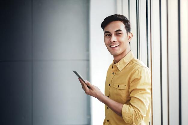 オフィスの窓のそばに立って幸せなビジネスマンの肖像画。スマートフォンを使用して笑顔。カメラを見て
