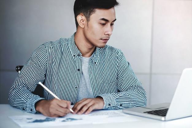 Молодой бизнесмен работая на компьтер-книжке компьютера в офисе.