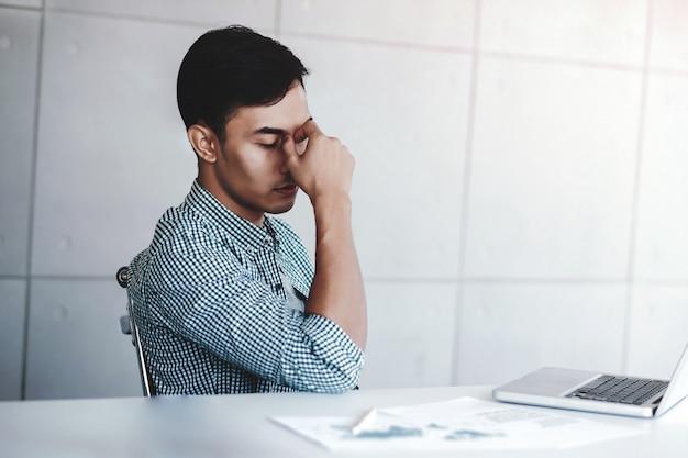 Бизнесмен утомленный и стресс молодой сидя на столе в офисе с компьтер-книжкой компьютера.