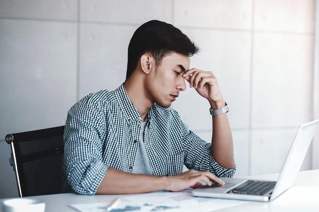 コンピューターがオフィスの机の上に座って疲れやストレス青年実業家