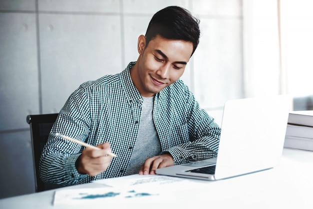 幸せな青年実業家のオフィスでコンピューターのラップトップに取り組んでいます。笑みを浮かべて紙に書く