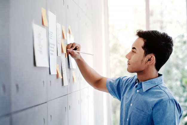 Молодой азиатский бизнесмен работая в конференц-зале офиса.