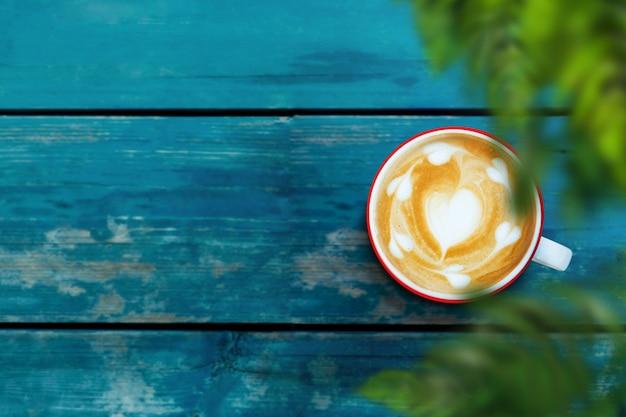 Чашка кофе латте на деревянный стол. отдых с горячим напитком. вид сверху