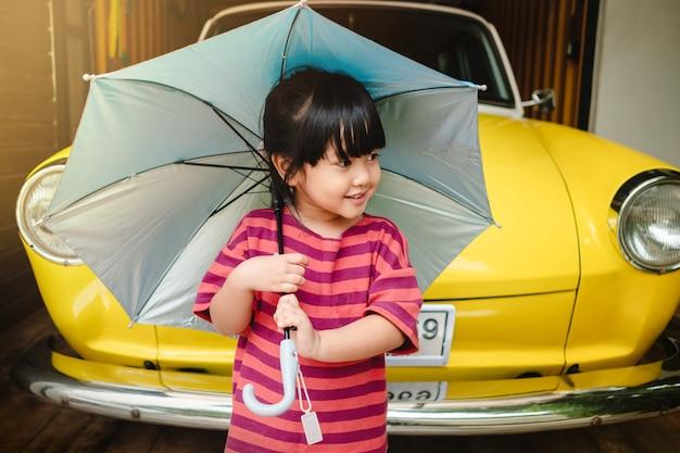 傘を持つ幸せな子供たちの肖像画。夏の雨や日光を守る