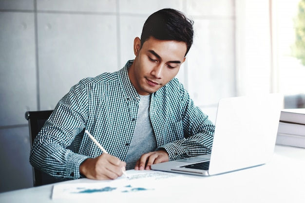 幸せな青年実業家のオフィスでコンピューターのラップトップに取り組んで