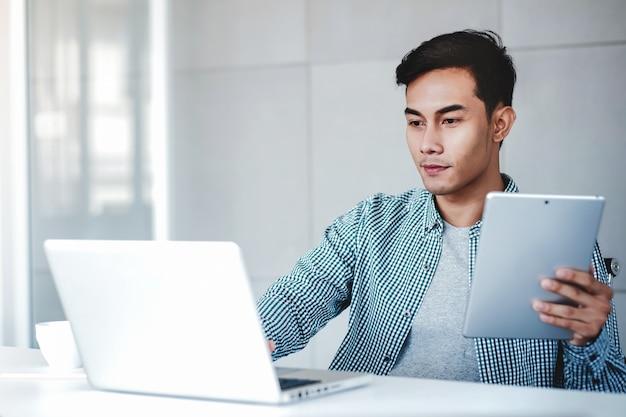オフィスでコンピューターのラップトップとデジタルタブレットに取り組んで幸せな青年実業家