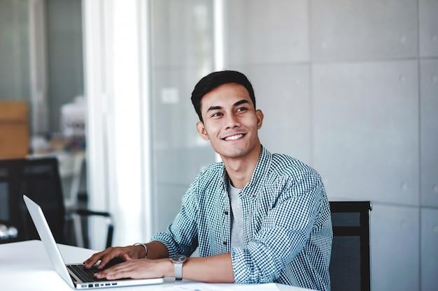 オフィスでコンピューターのラップトップに取り組んで幸せな青年実業家。笑顔で目をそらす