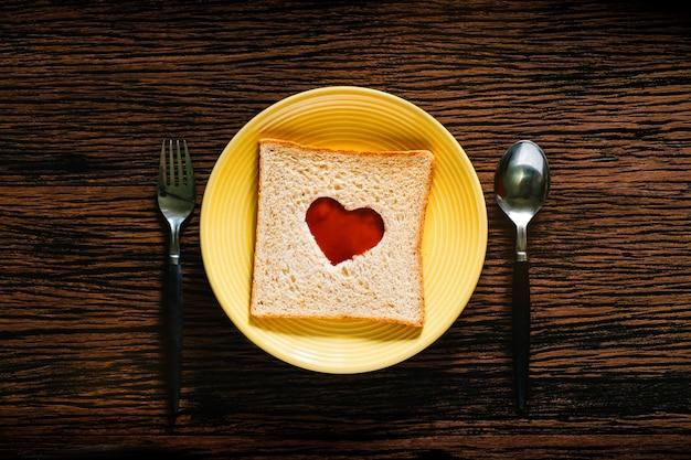愛とロマンスのコンセプト。朝食時にスプーンとフォークで皿の上のパン。パンのトマトソースとハート形。上面図