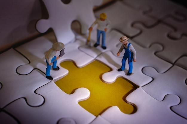 ミニチュア労働者の男性のグループが作業プロセスで何か間違ったことを発見