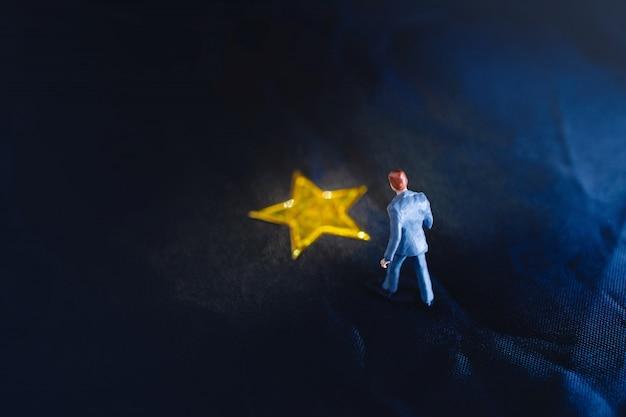 黄色の黄金の星の上に立っているミニチュア実業家のトップビュー