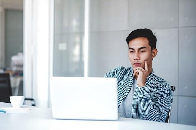 オフィスでコンピューターのラップトップに取り組んで真剣に青年実業家