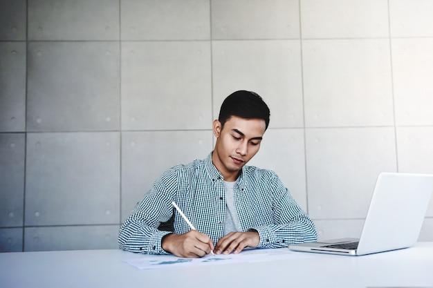 オフィスでコンピューターのラップトップに取り組んでいる青年実業家