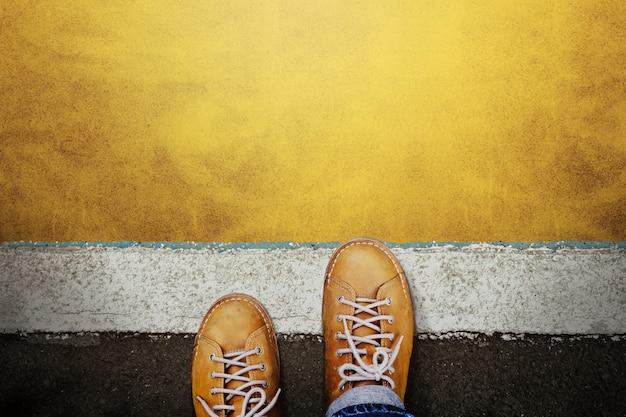 カジュアルレザーシューズの男性がスタートラインに足を踏み入れ、前進する準備をするか、成功のチャンスを取ります。