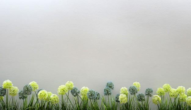 コンクリートの壁にコピースペースと春の花の国境