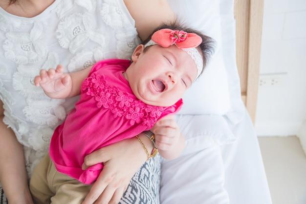 小さなアジア人の新生児が寝室で抱く母親の間に泣いている