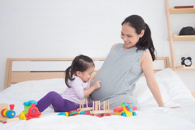 彼女の妊娠中の母親の腹と笑顔を指している少女