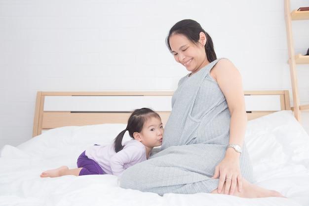 彼女の妊娠した母親の腹をベッドで家にキスする少年のアジアの女の子