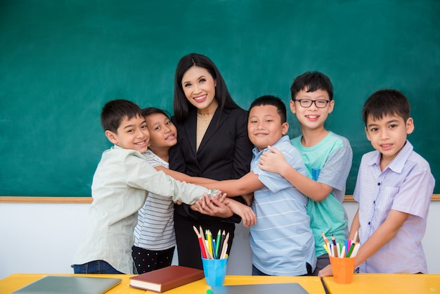 教室で教師を抱擁するアジア学生のグループ