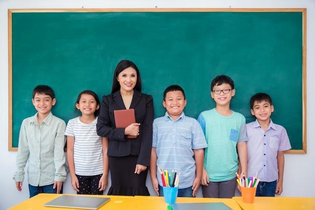 幸せなアジアの学生と教室に立っている教室のグループ