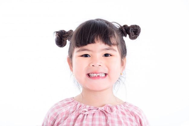 小さなアジアの女の子の笑顔と白い背景の上に彼女の最初の歯の損失を示す