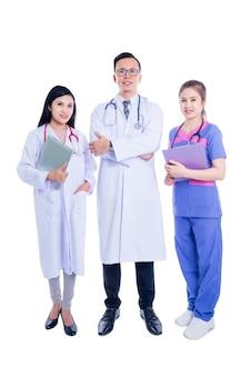 白い背景の上に孤立した立っている若いアジア医療チームのグループ