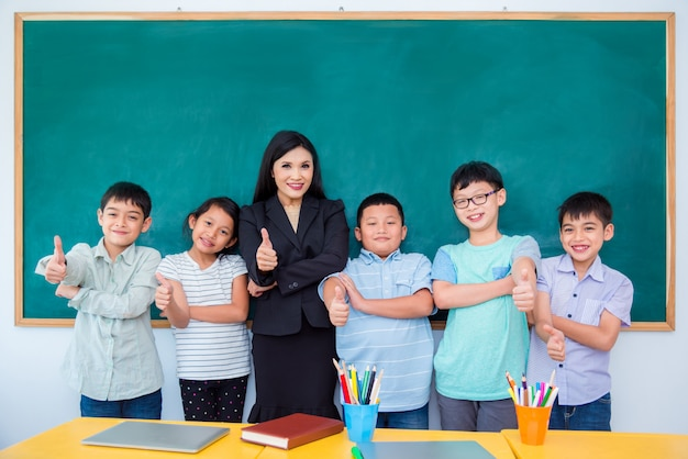 幸せなアジア学生と教室に立っている先生のグループ
