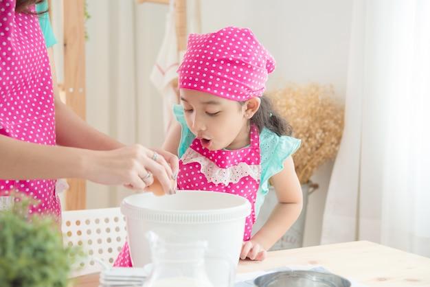 母と娘は台所でケーキを作るピンクのエプロンを着ています。