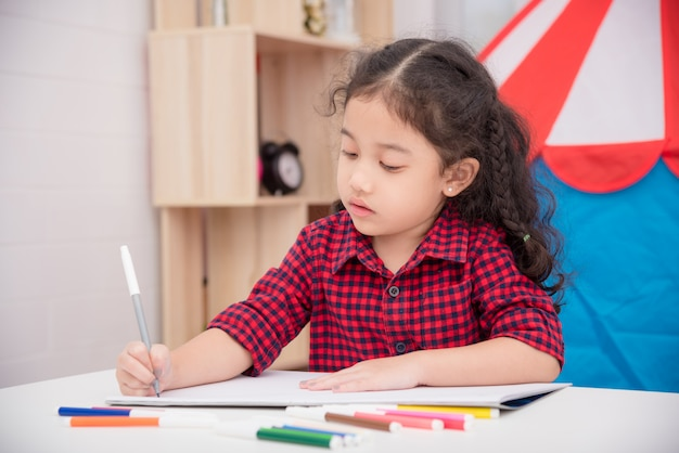 自宅でテーブルの上のカラーマーカーで絵を描く小さなアジアの女の子