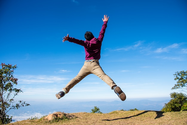 健康的な若い男が美しい山を背景に空中でジャンプします。