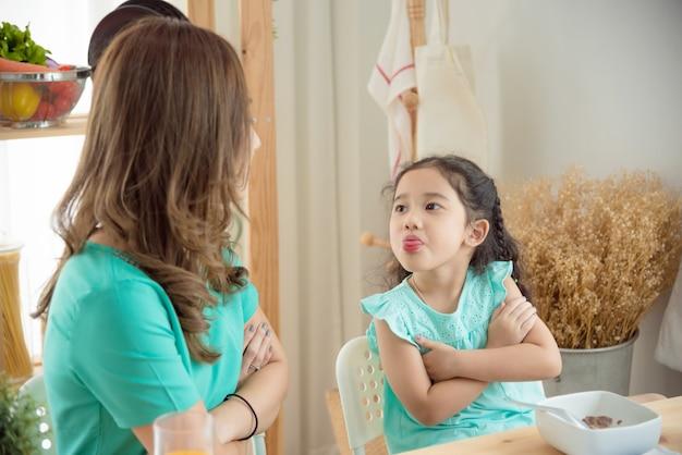 小さなアジアの女の子は彼女の母親と一緒に朝食をとることを拒否