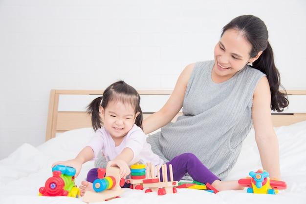Маленькая азиатская девушка играя игрушки с ее матерью